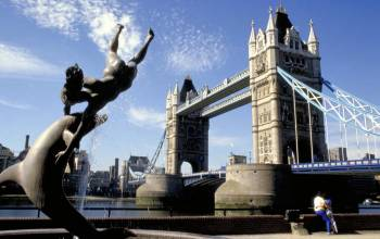 Statue of a dolphin playing with a boy next to Tower Bridge and the River Thames